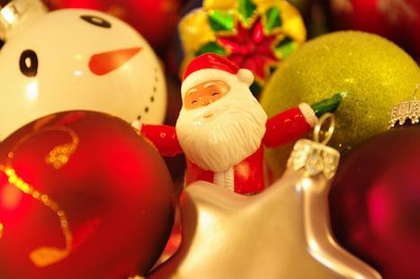 Weihnachtsmannfigur umrahmt von Christbaumkugeln